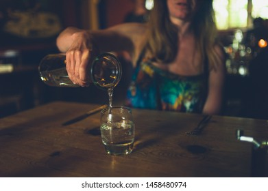 A young woman is pouring herself a glass of water in a restaurant