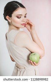 A young woman in a powder color dress is standing and holding a big green apple in her hand.