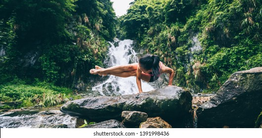 Young woman practice yoga in side crane position near waterfall in forest