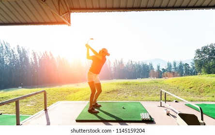 Young woman practices her golf swing on driving range, view from behind
