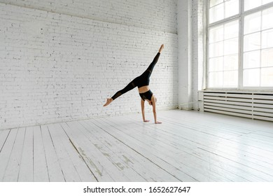 A young woman practices inversion balancing yoga pose stand