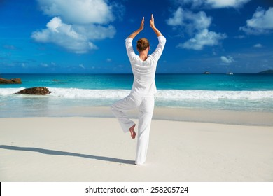 Young woman practices morning exercises on the beach
