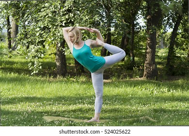 Young woman practices yoga and gymnastics in the park