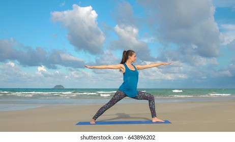 Young woman practices yoga on a beach at sunrise. Healthy lifestyle