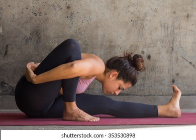 Young woman practicing advance yoga in front of a urban wall