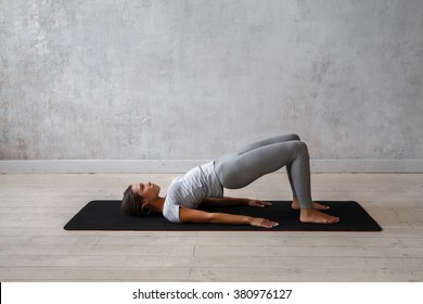 Young woman practicing advanced yoga. Bridge Pose. Setu Bandha Sarvangasana