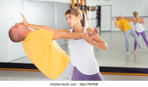 Young woman practicing basic self-defense techniques while training in gym with male partner, performing palm heel strike in chin..