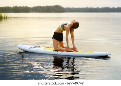Young woman practicing  Camel yoga Pose on paddle board in the early morning