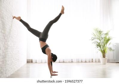 Young woman practicing downward facing tree asana in yoga studio. Adho Mukha Vrksasana pose