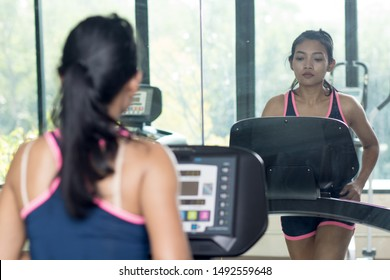 Young woman practicing in the gym with mirrors. Girl running on treadmill at fitness club.