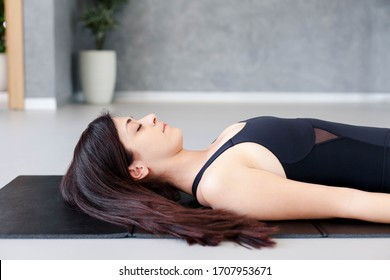 Young woman practicing hatha yoga at home. Girl doing morning exercises. Shavasana or savasana in cozy room. Concept of healthy lifestyle, relaxation, wellbeing. Female fitness classes. Close up