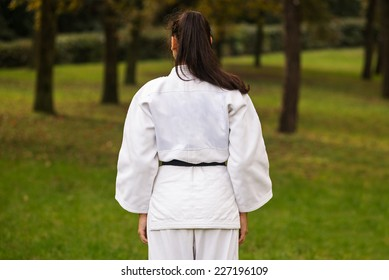 Young woman practicing judo back portrait outdoors in a park.