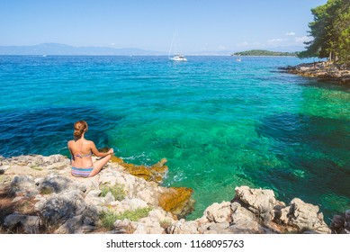 Young woman practicing morning meditation in nature at the beach. Caucasian woman practicing yoga at seashore near Malinska on island Krk, Croatia.