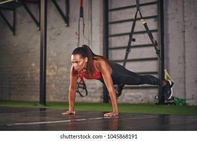 Young woman practicing on trx ropes