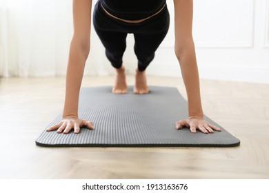 Young woman practicing plank asana in yoga studio, focus on hands. Phalakasana pose