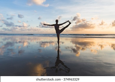 Young woman practicing pose from yoga on the beach at sunset