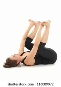 young woman practicing relaxation yoga pose, full side view, dressed in black, on white background