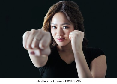 Young woman practicing self defense throws a punch