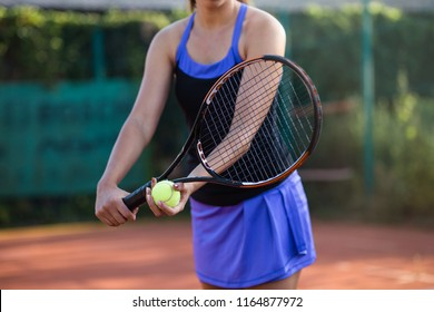 Young woman practicing serve on outdoor tennis court.