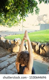 Young woman practicing yoga asana in tropical park. Healthy lifestyle and doing exercises concept.