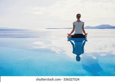 Young woman practicing yoga. Beautiful girl meditating, doing breathing exercises. Harmony, balance, meditation, relaxation, mindfulness, recreation, self care, body care, healthy lifestyle concept
