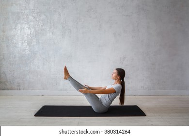 Young woman is practicing yoga. Boat Pose Variation. Navasana