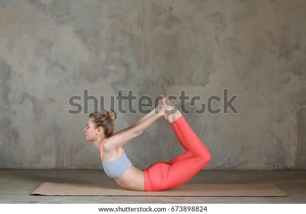 Young woman practicing yoga Bow pose, Dhanurasana against texturized wall / urban background
