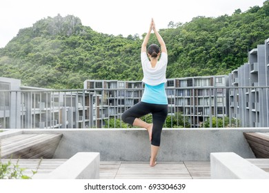 Young woman is practicing yoga at building