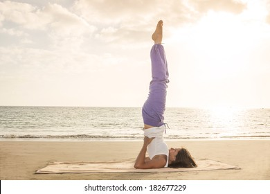 Young woman practicing yoga candle pose on the beach near the ocean at sunset