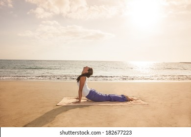 Young woman practicing yoga cobra pose on the beach near the ocean at sunset