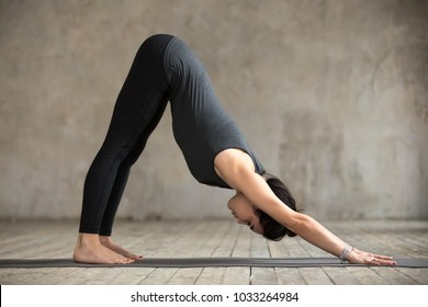 Young woman practicing yoga, doing Downward facing dog exercise, adho mukha svanasana pose, working out, wearing sportswear, black pants and top, indoor full length, gray wall in yoga studio