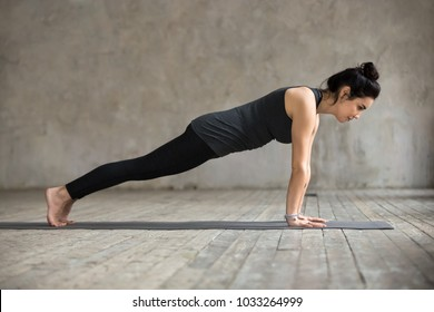 Young woman practicing yoga, doing Push ups or press ups exercise, phalankasana, Plank pose, working out, wearing sportswear, black pants and top, indoor full length, gray wall in yoga studio