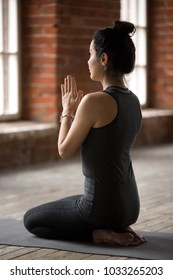 Young woman practicing yoga, doing seiza exercise, vajrasana pose, working out, wearing sportswear, black pants and top, indoor full length, yoga studio, rear view