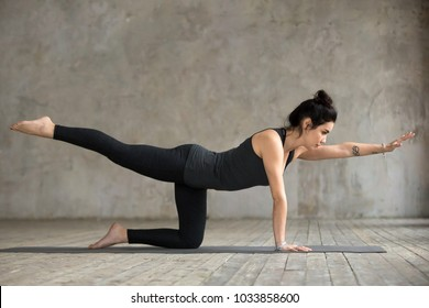 Young woman practicing yoga, doing Donkey, Kick exercise, Bird dog pose, working out, wearing sportswear, black pants and top, indoor full length, gray wall in yoga studio