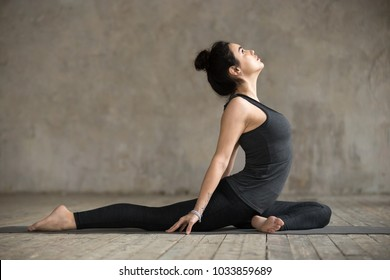 Young woman practicing yoga, doing Single Pigeon, Eka Pada Raja Kapotasana exercise, One Legged King Pigeon pose, working out, wearing sportswear, indoor full length, gray wall in yoga studio
