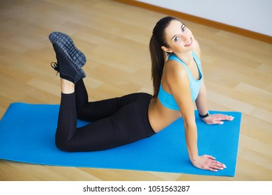 Young woman practicing yoga, doing Wild Thing, Flip-the-Dog exercise, Camatkarasana pose, working out, wearing sportswear, black pants and top, indoor full length, gray wall in yoga studio