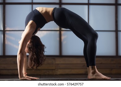 Young woman practicing yoga, doing Wild Thing, Flip-the-Dog pose, Camatkarasana, variation of Bending Side Plank exercise, Vasisthasana, working out, wearing sportswear, black tank top, pants