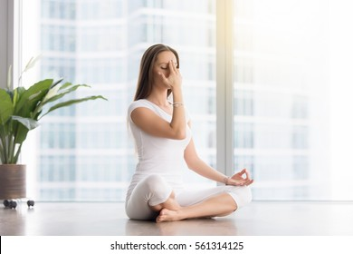 Young woman practicing yoga exercise, sitting in Sukhasana pose, Alternate Nostril Breathing technique, nadi shodhana pranayama, working out, wearing white sportswear, indoor full length