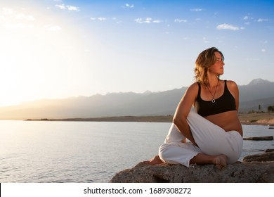 Young woman is practicing yoga in Half Lord of the Fishes Pose (Matsyendra) pose at mountain lake.
