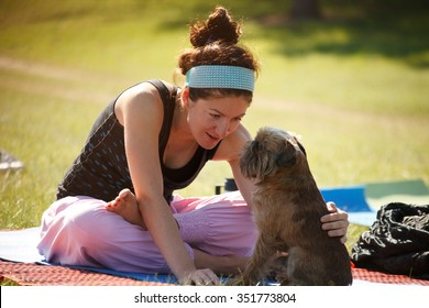 Young woman is practicing yoga with her dog