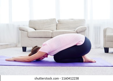 Young woman practicing yoga at home indoor, copy space. Girl relax meditation in child's pose, full length. Relaxing and doing yoga, resting, stretching. Wellness and healthy lifestyle. Balasana