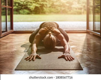 Young woman practicing yoga at home - Shutterstock ID 1808567716