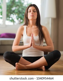 Young Woman Practicing Yoga In The Lotus Position, Indoors