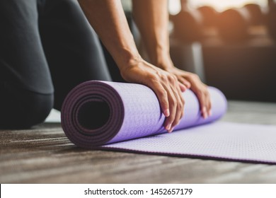Young woman practicing yoga and meditating indoors. Beautiful girl preparing material for practice class. Calmness and relaxation. Female happiness concept. Horizontal blurred background.