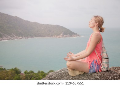 Young woman practicing yoga and meditation in mountains during luxury yoga retreat