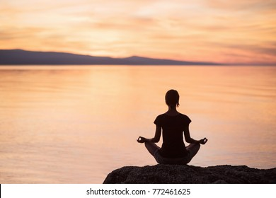 Young woman practicing yoga near the sea at sunset. Harmony and meditation concept. Healthy lifestyle