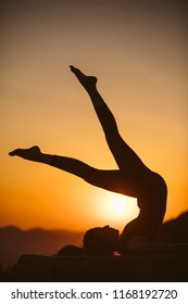 Young woman is practicing yoga on the mountain at sunset. Silhouette of young woman practicing yoga outdoor.