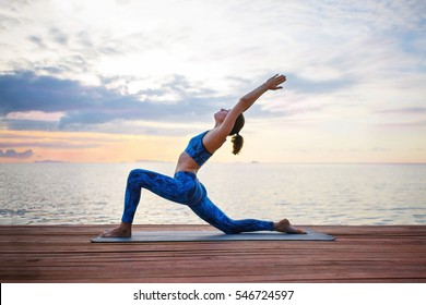 Young woman practicing yoga on the sunset beach