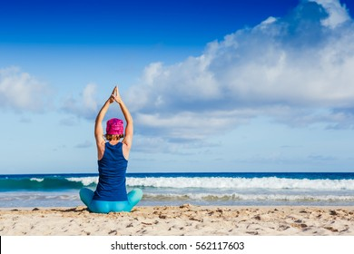 young woman practicing yoga on the beach for zen, health and peaceful lifestyle