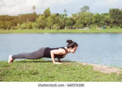 Young woman practicing yoga on green grass in the park.